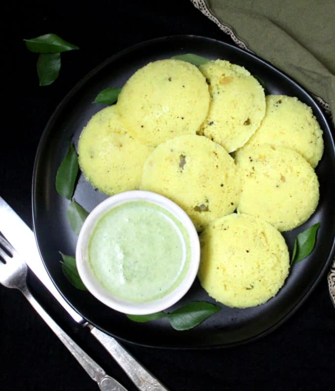 A black plate with fluffy, soft, spongy south Indian rava idlis with turmeric and a green cilantro coconut chutney with silverware and a green and gold napkin on the side.