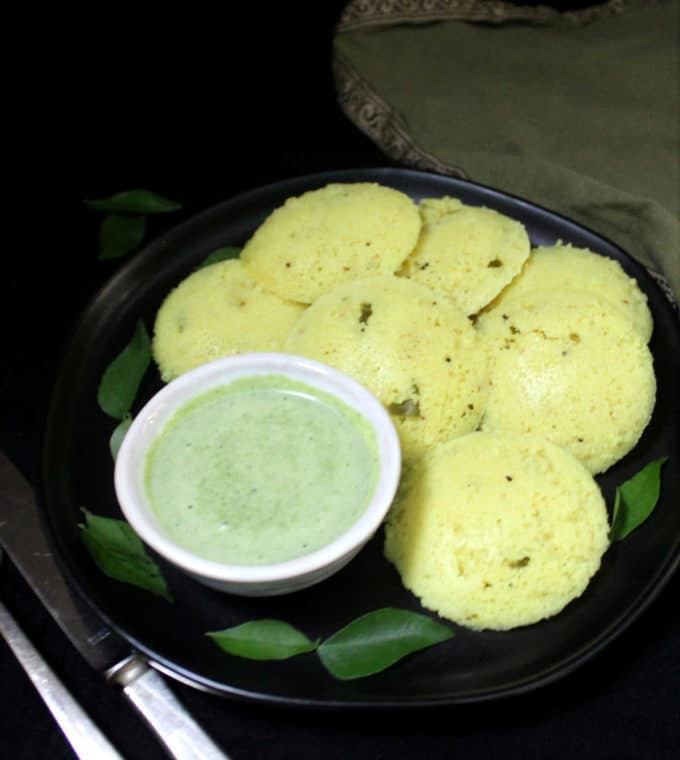 A black plate with many fluffy, spongy south Indian rava idlis with turmeric and a green cilantro coconut chutney.