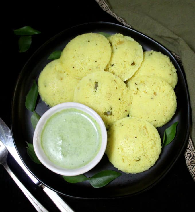 Overhead shot of soft, fluffy, spongy south Indian rava idlis with turmeric and a green cilantro coconut chutney on a black plate with silverware.