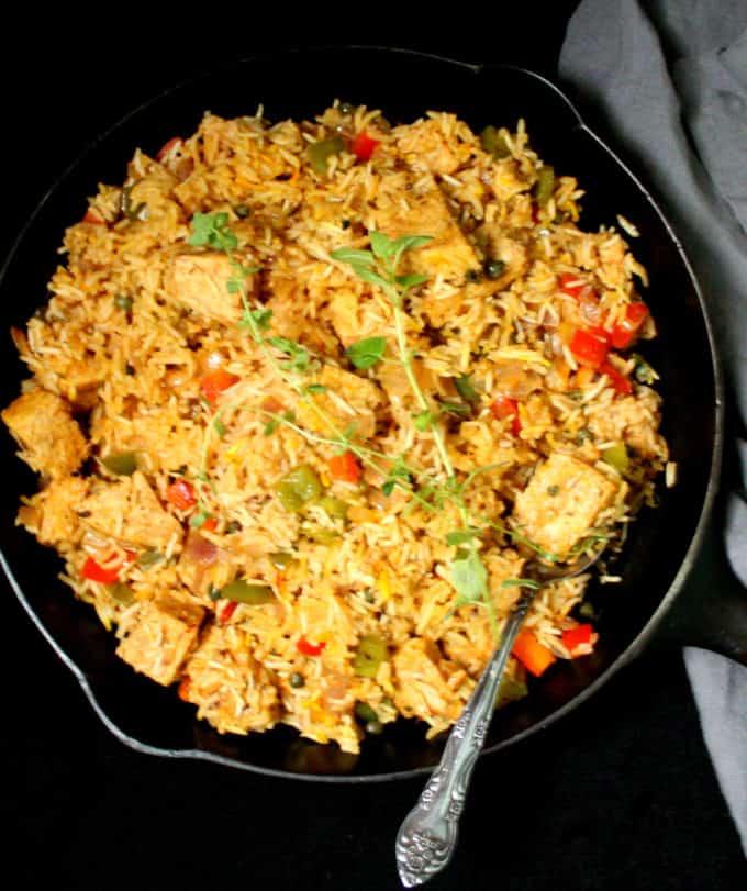 Foto aérea de uma chapa de ferro fundida com arroz con pollo vegan, ou frango espanhol e arroz com uma colher de prata decorativa e guardanapo cinza.