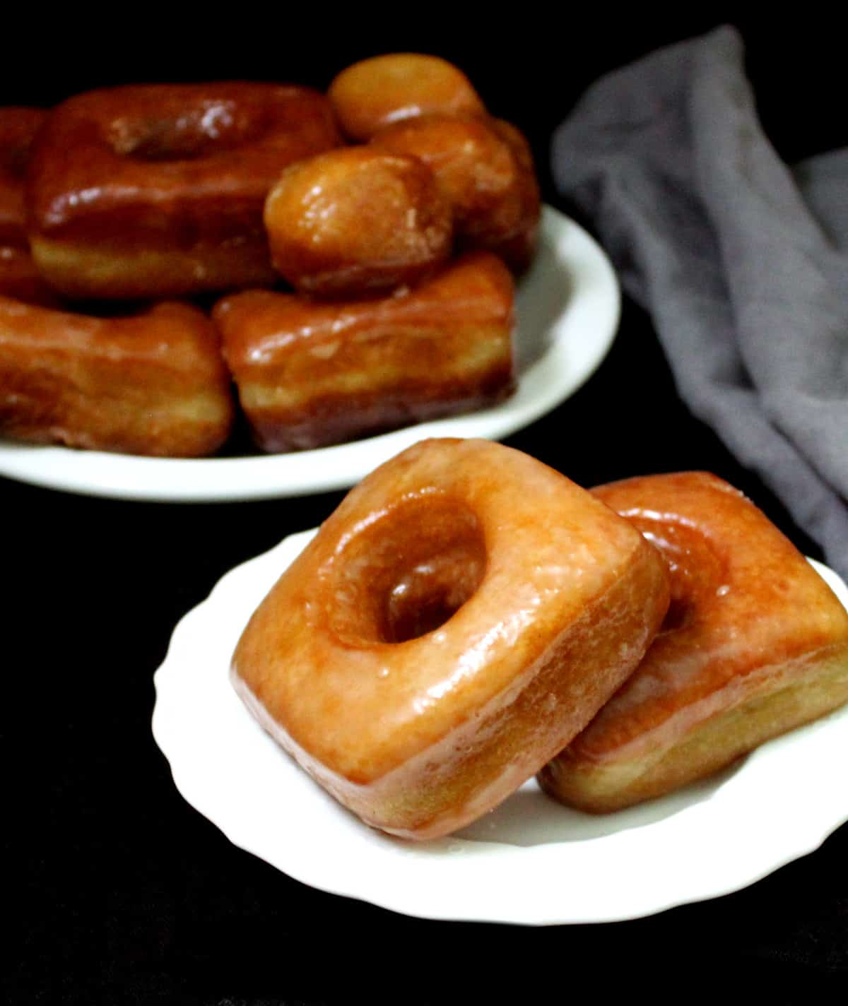 A close up of two vegan brioche donuts on a white plate with a stack of donuts and doughnut holes in the background, and a gray napkin on a black background.