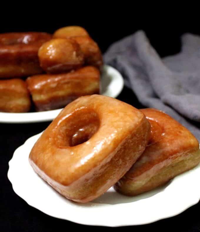 Tiro frontal de dois donuts quadrados com uma pilha de donuts em um prato branco e um guardanapo cinza.