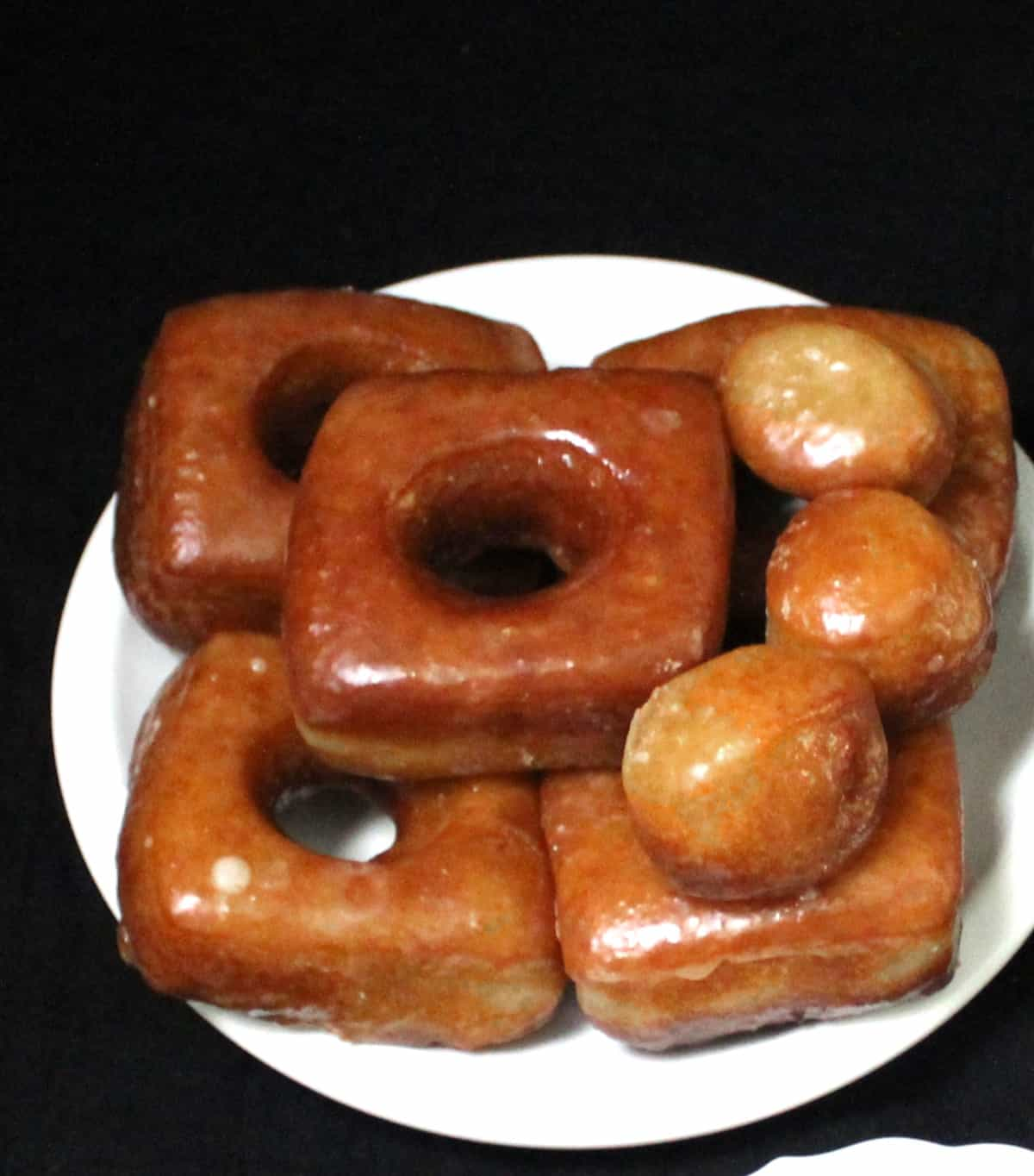 An overhead shot of a white plate stacked with square and round donuts with donut holes on a black background.