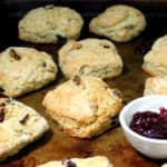 A closeup of several baked vegan cranberry sourdough scones on a baking sheet with raspberry jam
