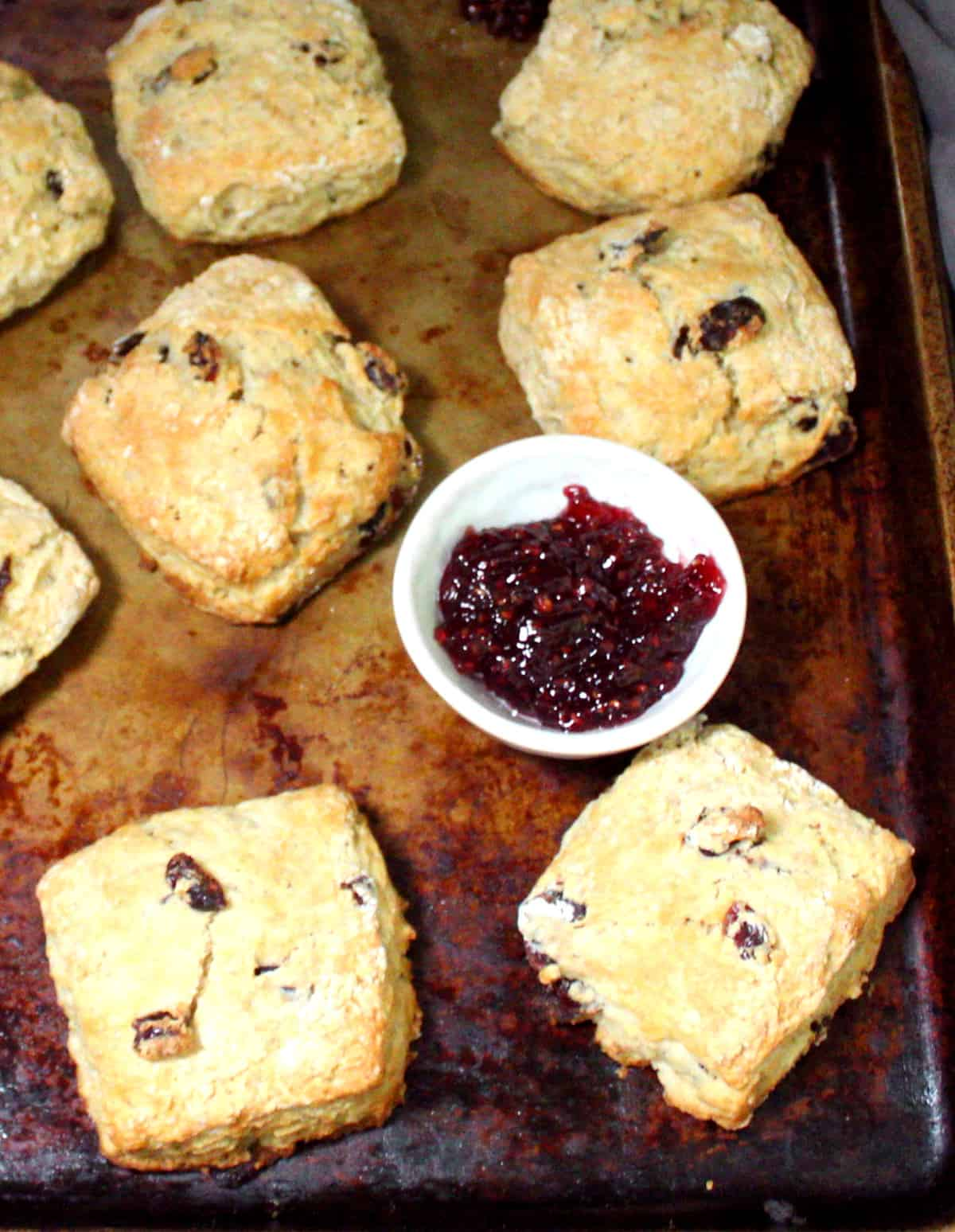Overhead close up shot of golden, crispy, tender vegan cranberry sourdough scones on a baking sheet with a small white bowl of raspberry jam.