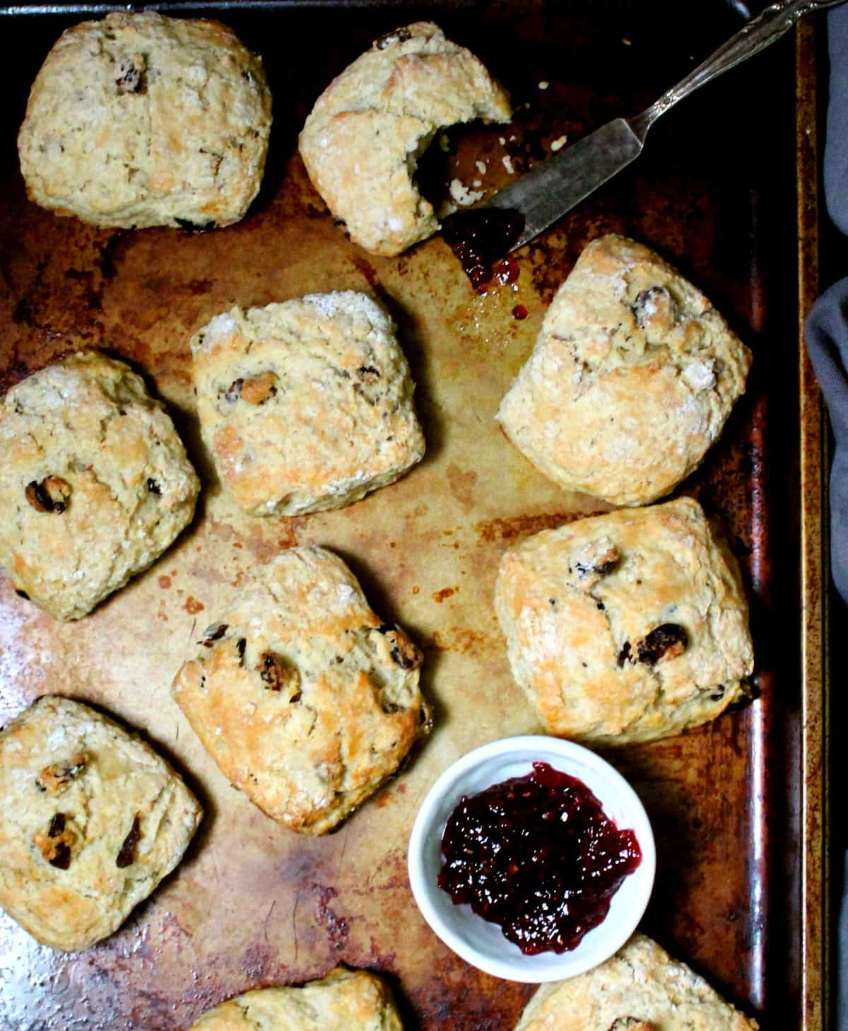 Overhead shot of golden, crispy, tender vegan cranberry sourdough scones on a baking sheet with a small white bowl of raspberry jam.