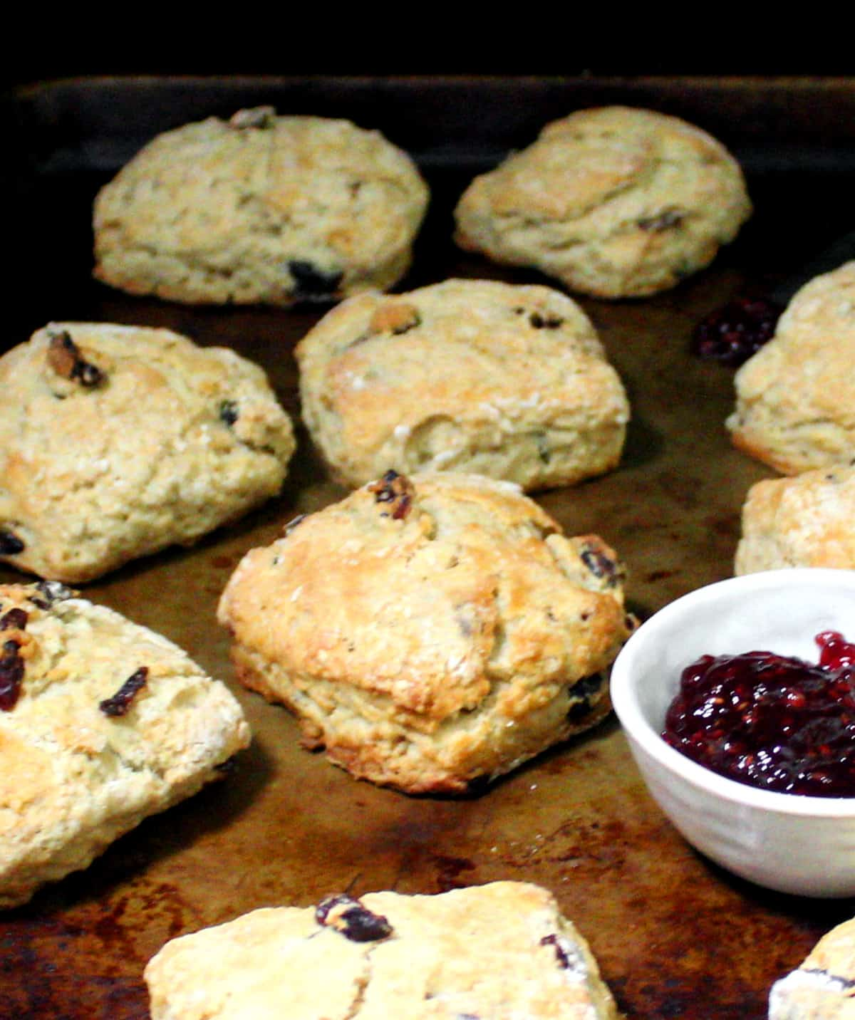 A close up shot of golden, crispy, tender vegan cranberry sourdough scones on a baking sheet with a small white bowl of raspberry jam.
