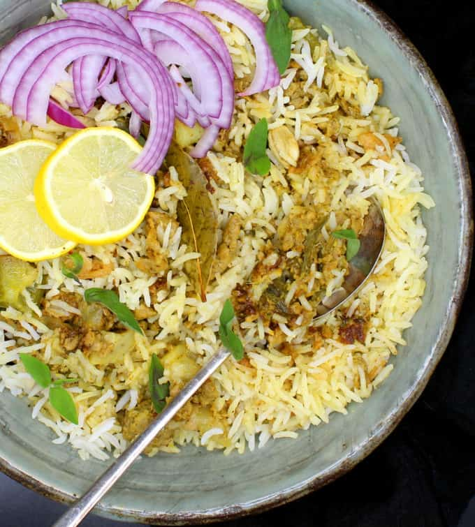 Partial overhead shot of a bowl of keema biryani, an Indian rice dish with ground meatless meat and spices, in a glazed bowl with a spoon, lemons and sliced onions