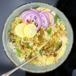 Overhead shot of a bowl of keema biryani, an Indian rice dish with ground meatless meat and spices, in a glazed bowl with a spoon, lemons and sliced onions
