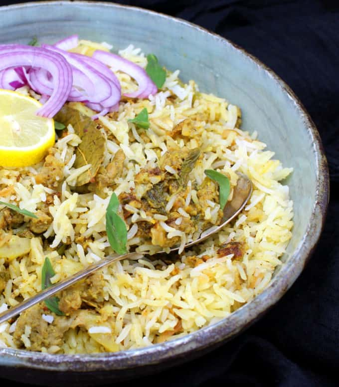 Partial front shot of a bowl of keema biryani, an Indian rice dish with ground meatless meat and spices, in a glazed bowl with a spoon, lemons and sliced onions