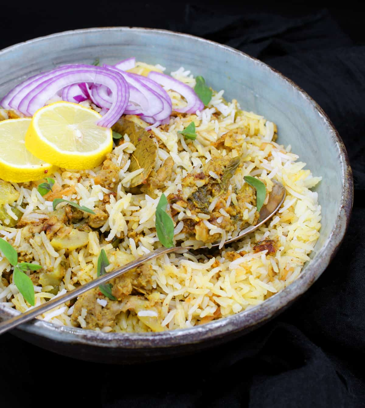 Front partial shot of a bowl of keema biryani, an Indian rice dish with ground meatless meat and spices, in a glazed bowl with a spoon, lemons and sliced onions