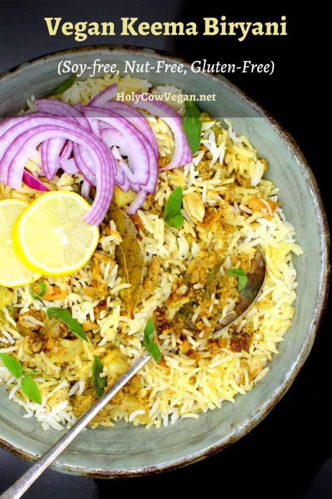 A bowl of keema biryani, an Indian rice dish with ground meatless meat and spices, in a glazed bowl with a spoon, lemons and sliced onions