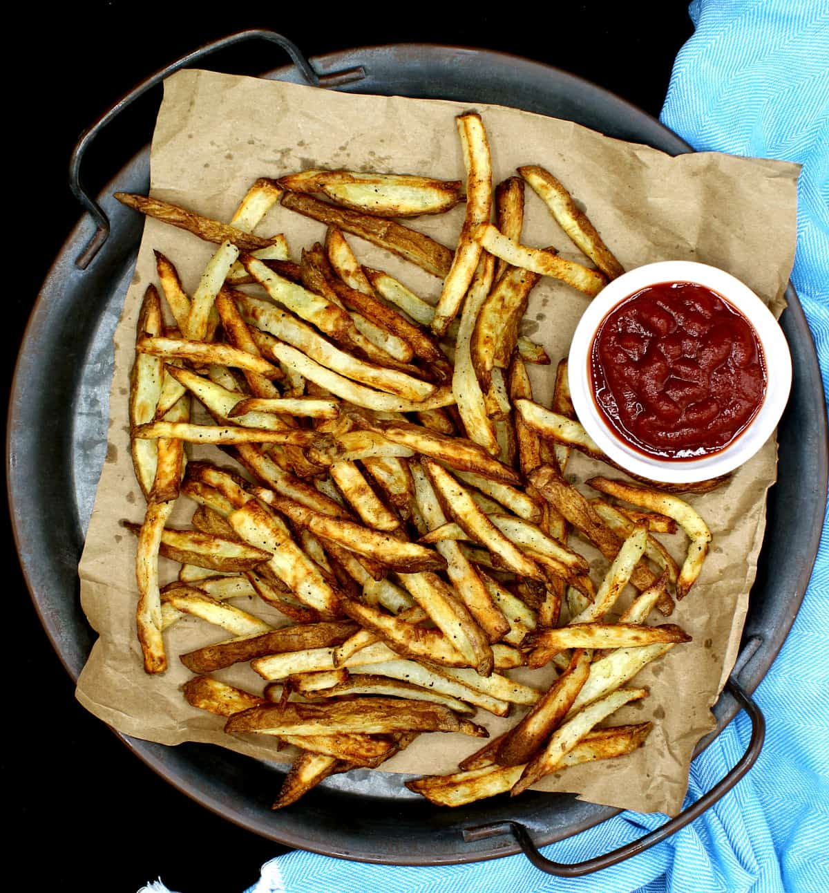 A top shot of air fryer French fries, golden and crispy, on brown paper. These are made with very little oil or no oil. Next to the fries is a white ceramic bowl with tomato ketchup.
