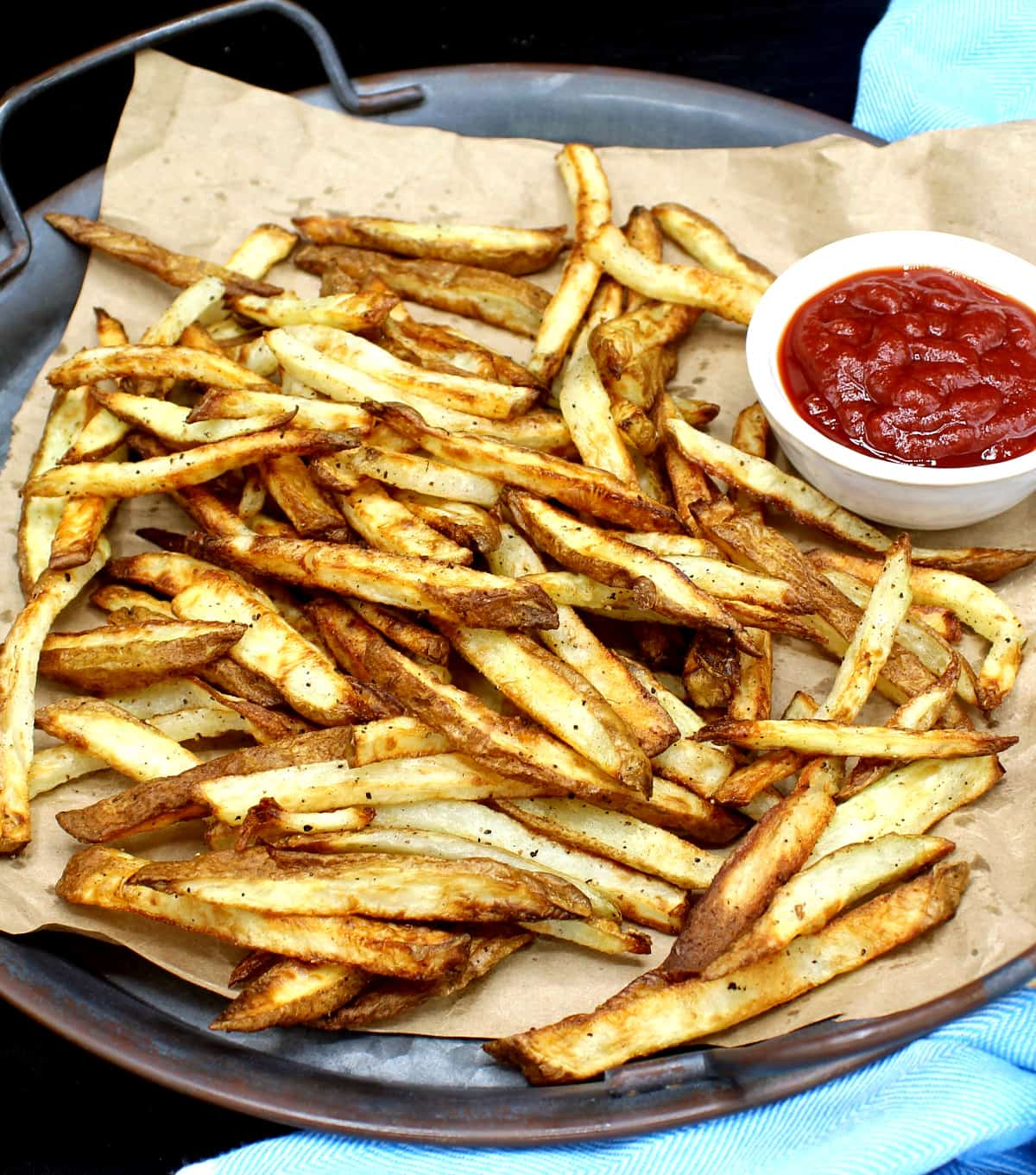 A closeup of air fryer French fries or pommes frites, golden and crispy, on brown paper. These are made with very little oil or no oil. Next to the fries is a white ceramic bowl with tomato ketchup.