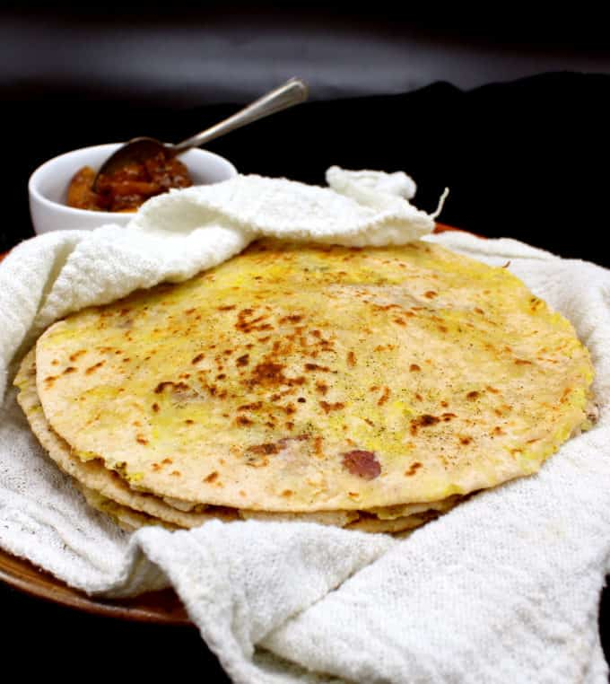 A front shot of a stack of freshly baked aloo parathas nestled in a white flour sack towel on an earthenware plate with a small white ceramic bowl of Indian lime pickle on the side, all on a black background.