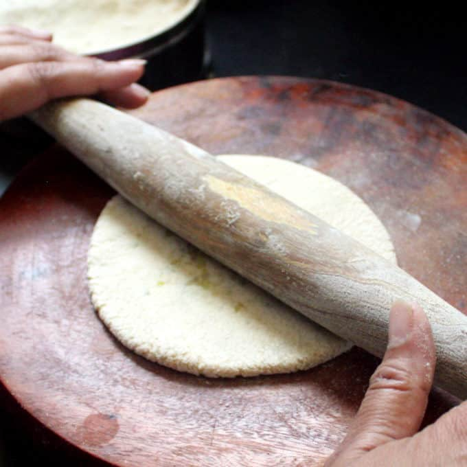 Aloo Paratha being rolled out on a wooden board with a rolling pin
