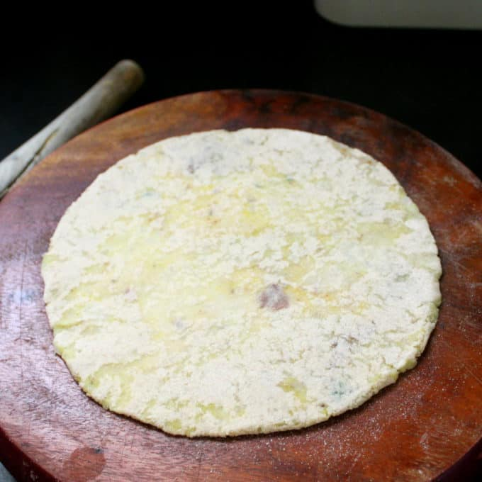 A rolled aloo paratha on a wooden board waiting to be roasted