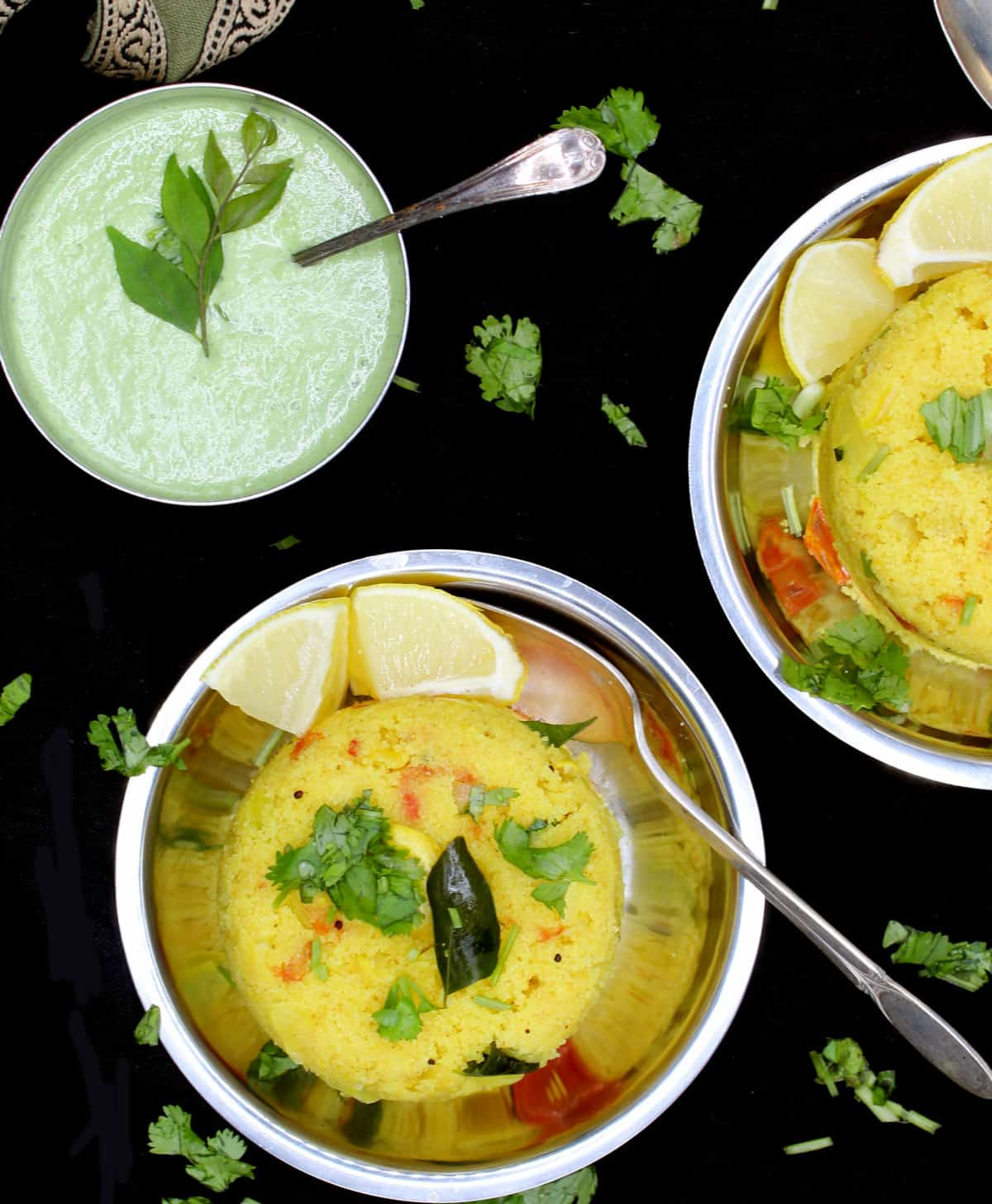 Overhead shot of a creamy green coconut chutney in a steel bowl with a spoon and garnished with curry leaves, served with south Indian upma in steel plates and garnished with cilantro and lemon, all on a black background.