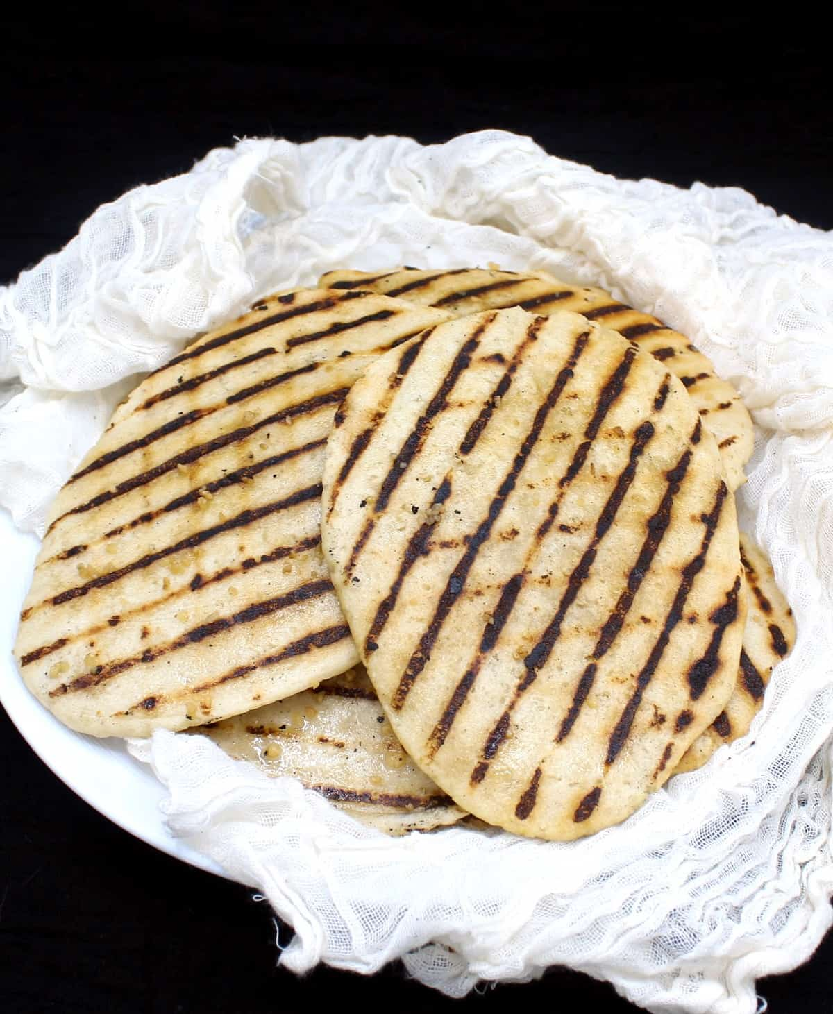 A stack of grilled vegan gluten free naans on a white plate wrapped in cheesecloth on a black background.