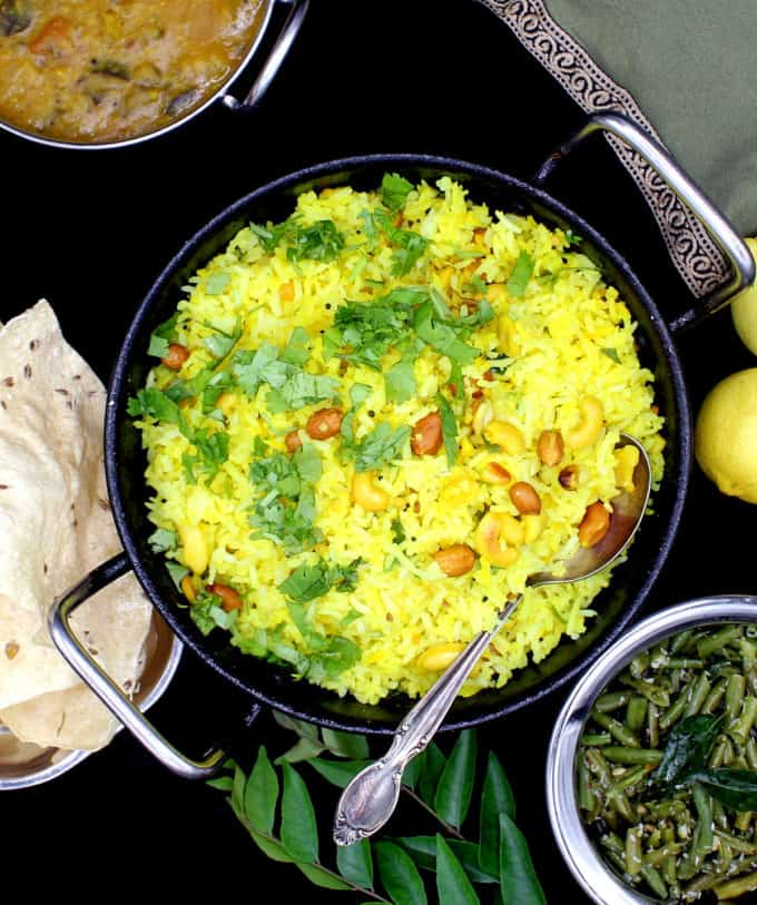 Overhead shot of a steel kadhai with bright yellow lemon rice with mustard seeds, cilantro, peanuts, cashews and red pepper, surrounded by a green bean curry, south Indian sambar and poppadum with curry leaves on the side. Also in the shot is a green and gold napkin and lemons on a black background.