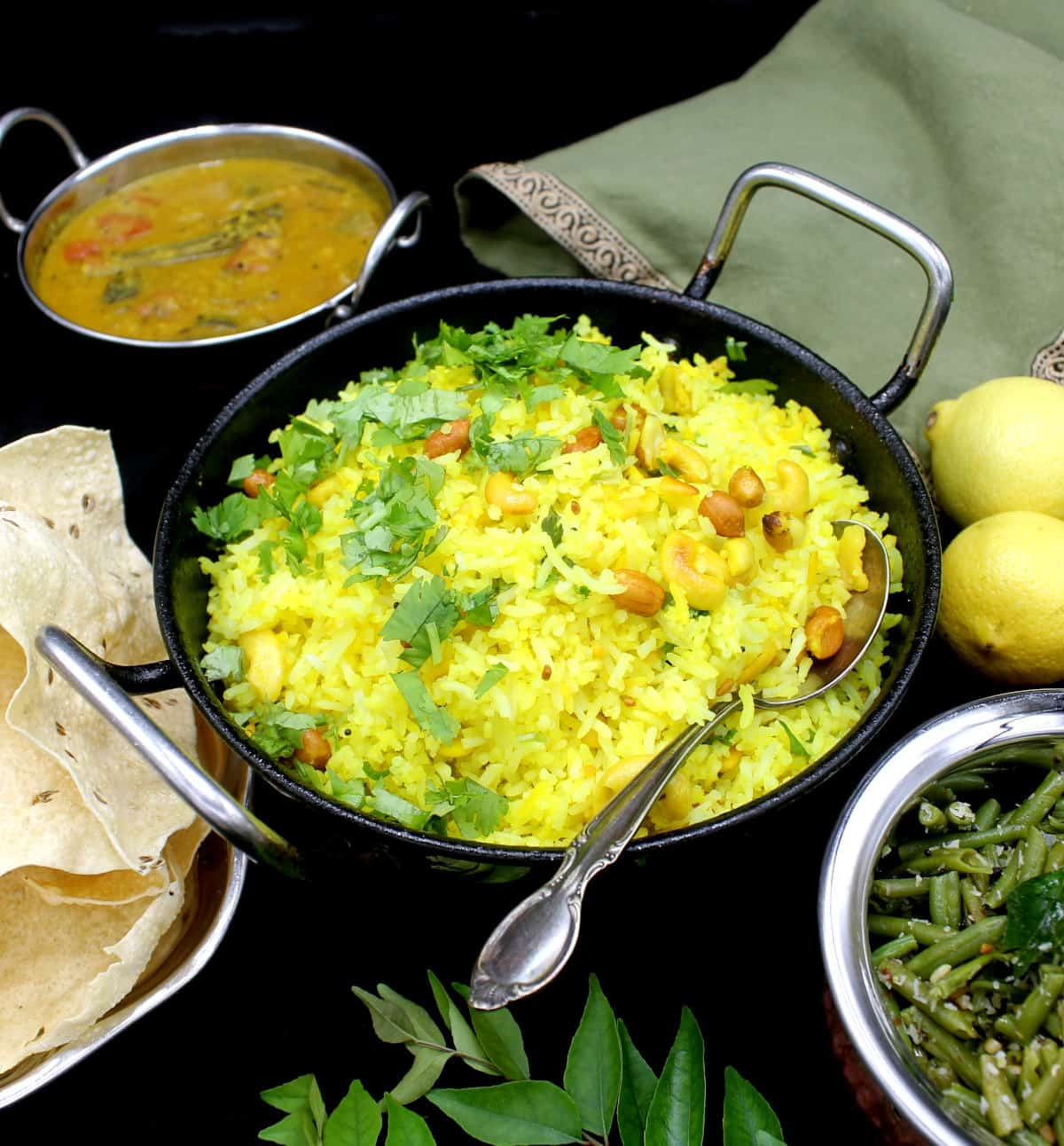 A front shot of a steel kadhai with bright yellow lemon rice with mustard seeds, cilantro, peanuts, cashews and red pepper, surrounded by a green bean curry, south Indian sambar and poppadum with curry leaves on the side. Also in the shot is a green and gold napkin and lemons on a black background.