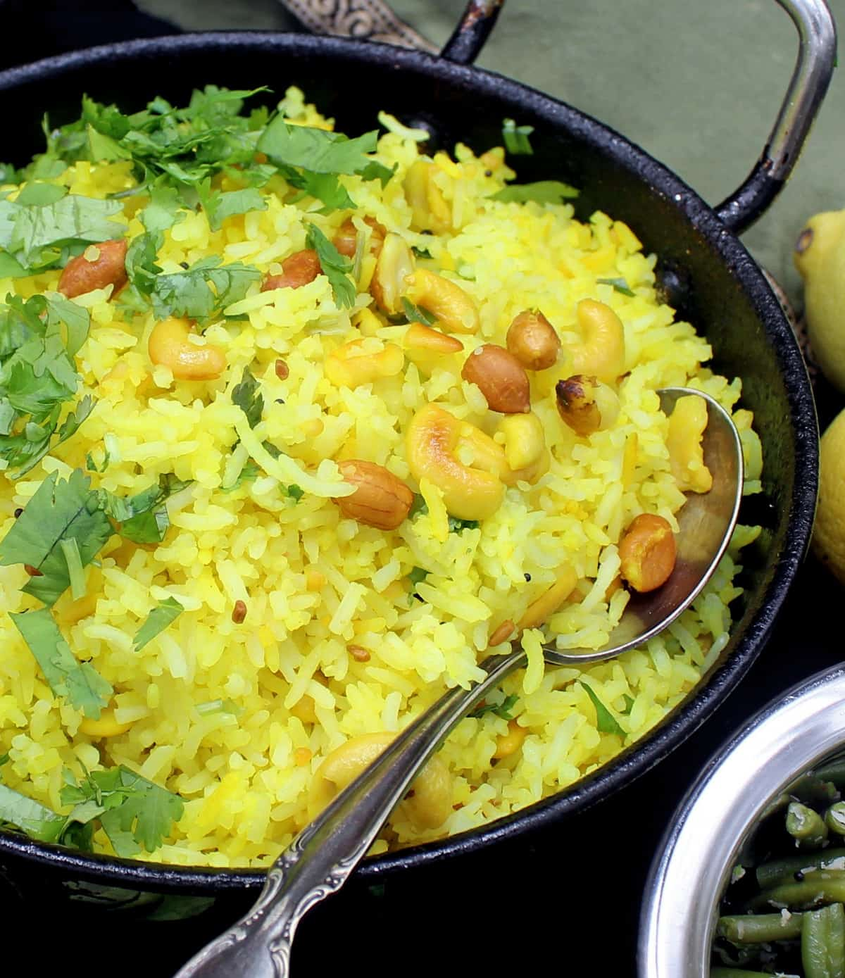 Tight closeup of a steel kadhai with bright yellow lemon rice with mustard seeds, cilantro, peanuts, cashews and red pepper, with a green bean curry next to it. Also in the shot is a green and gold napkin and lemons on a black background.