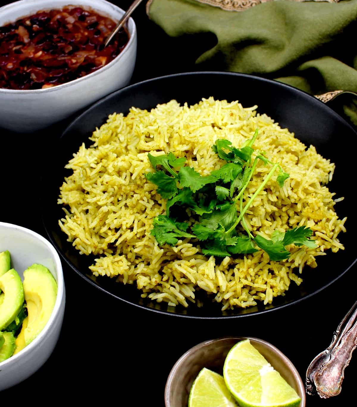 A front shot of a dinner table with a black bowl with Mexican green rice and cilantro, surrounded by wedges of lime, avocado and refried beans, In the background is a green napkin with gold border, and all of it is on a black background.