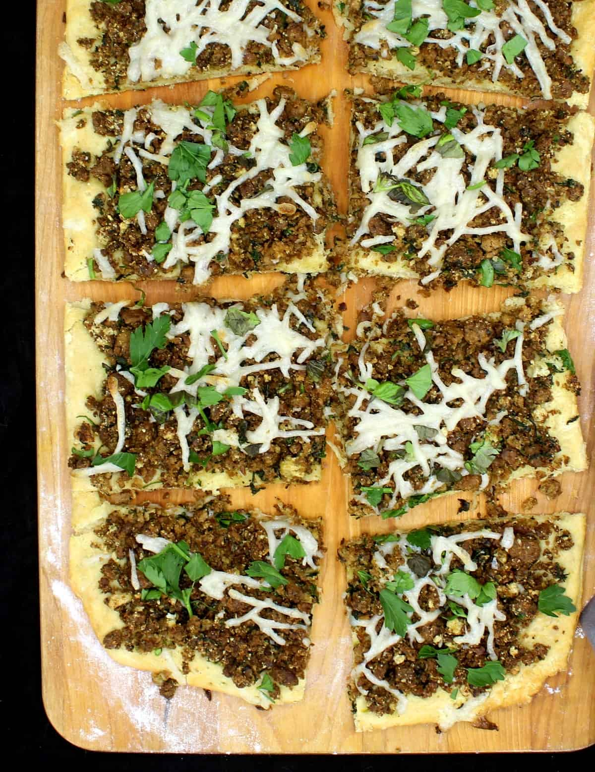 Slices of vegan breakfast sausage pizza with a biscuit crust with cheese and parsley and other herbs on a chopping board.