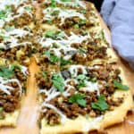 A closeup of slices of vegan breakfast sausage pizza with a biscuit crust with cheese and parsley and other herbs on a chopping board.