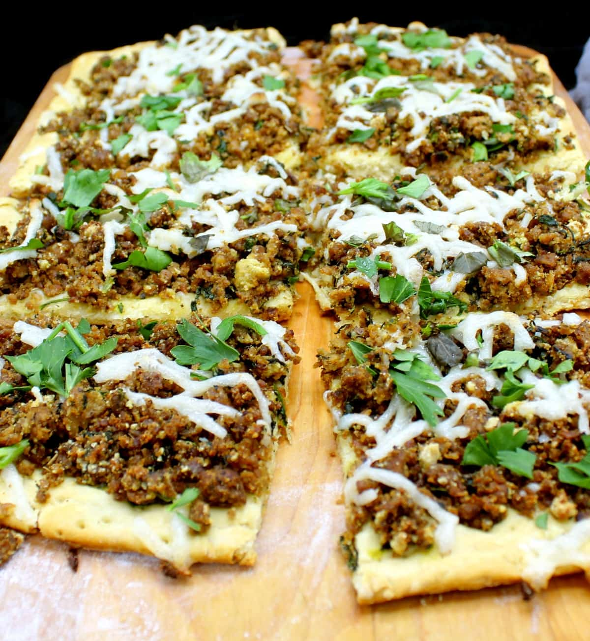 Slices of a rectangular vegan breakfast sausage pizza with a biscuit crust with cheese and parsley and other herbs on a chopping board.