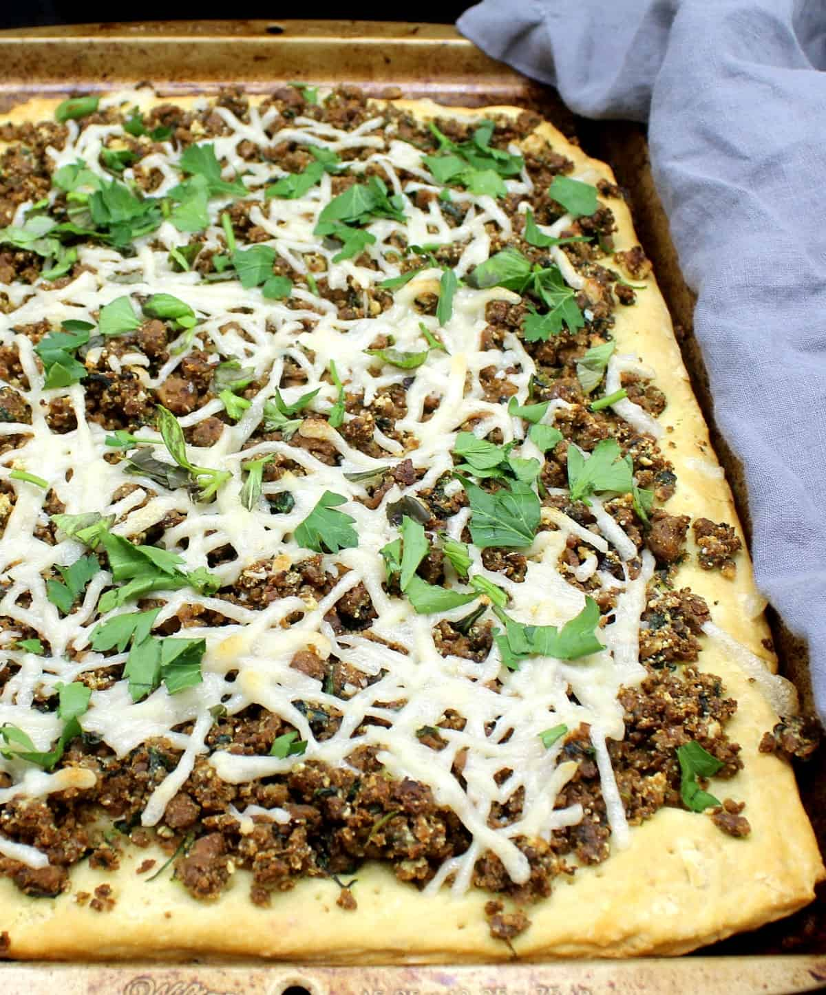 A closeup of vegan breakfast sausage pizza with a biscuit crust loaded with cheese and parsley and other herbs on a baking sheet.