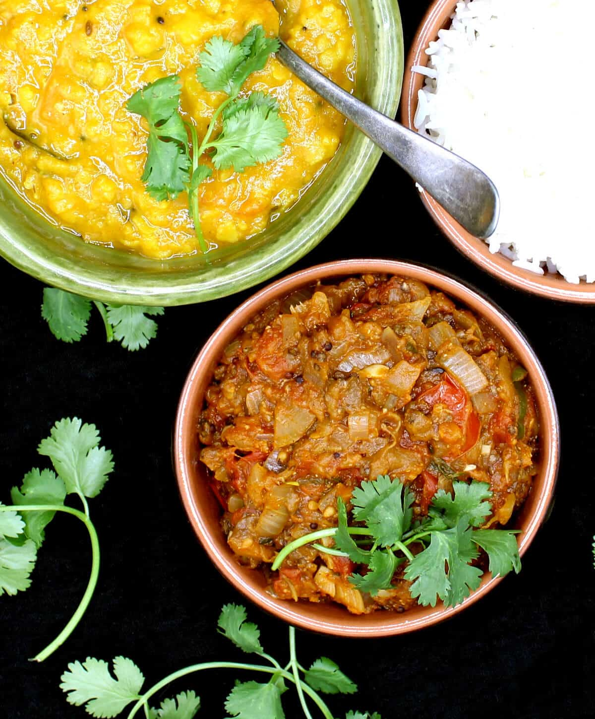A clay dish with Baingan Bharta, mashed eggplants in a tomato onion sauce, garnished with cilantro. Next to it are tomato dal and rice with a spoon.