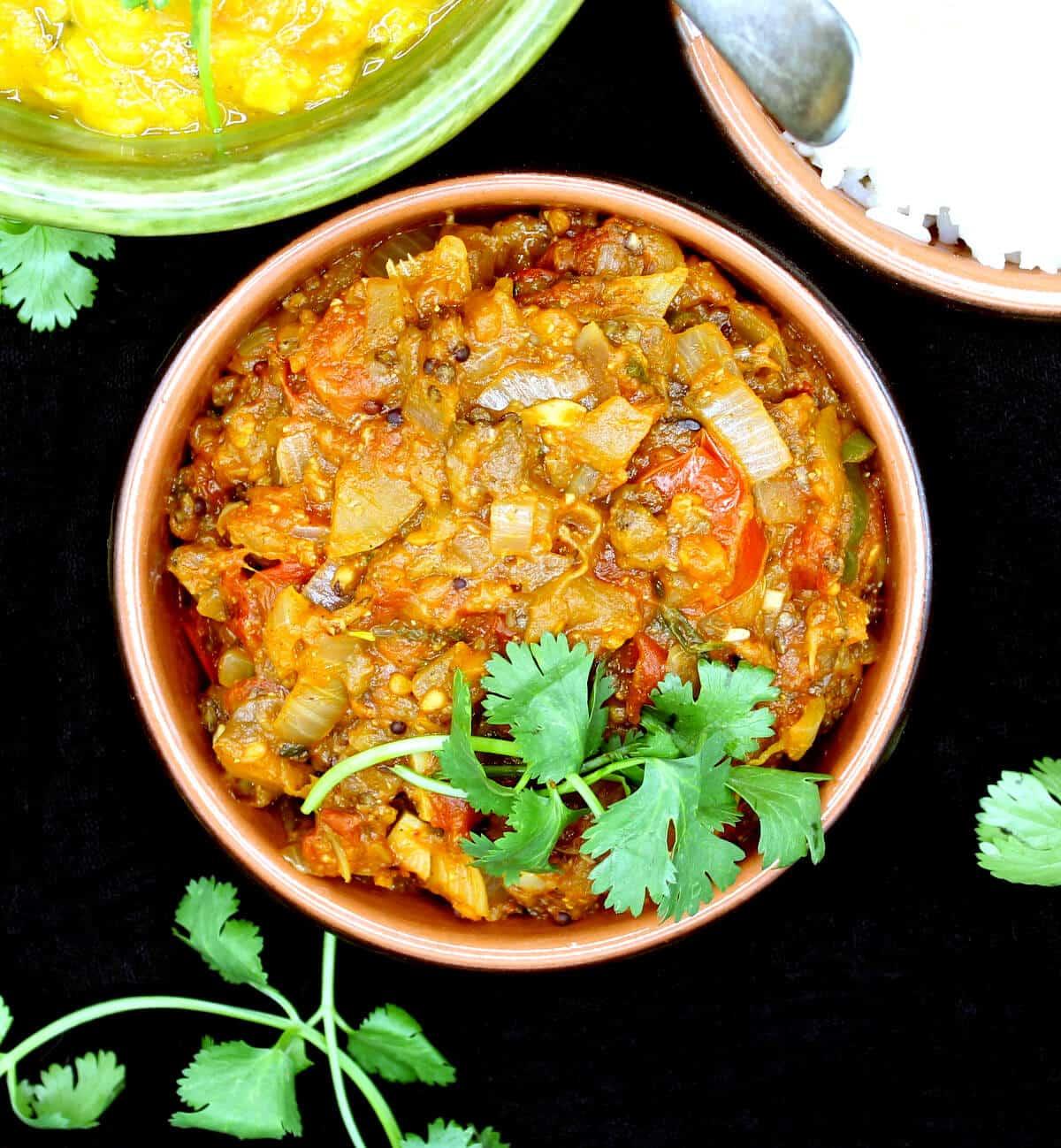 Um prato de barro de baingan bharta com coentro servido com arroz e dal.