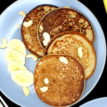 Banana dosas served with fresh slices of bananas on a gray ceramic plate with bananas and forks in the background with a cheesecloth