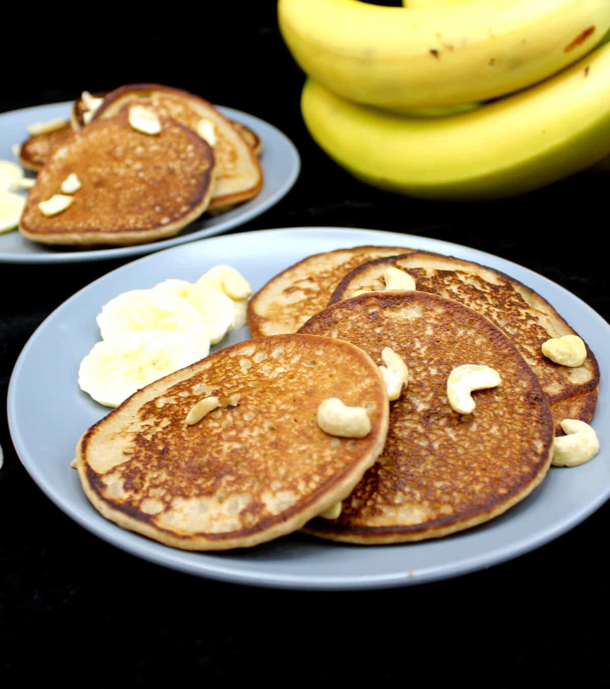 Banana dosas served with fresh slices of bananas on gray ceramic plates with bananas and forks in the background with a cheesecloth