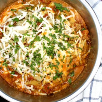 Vegan Instant Pot Lasagna with layers of marinara, ricotta, parmesan and mozzarella in an Instant Pot liner with parsley sprinkled on top and next to a blue and white kitchen towel.