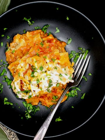 A slice of creamy, cheesy vegan Instant Pot Lasagna in a black bowl with a fork and parsley scattered around it