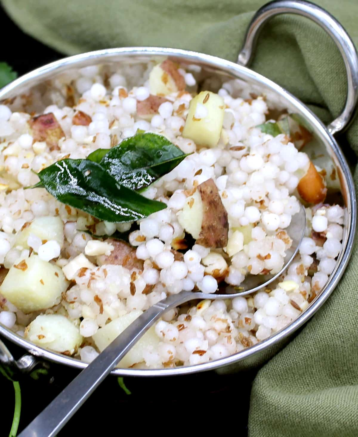 A steel wok or kadhai with sabudana khichdi, made with tapioca pearls, with a garnish of curry leaves, peanuts, potatoes and with cilantro leaves scattered around. Next to the wok is a green and gold napkin on a black background.