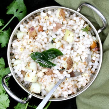 A steel wok with sabudana khichdi garnished with cilantro, curry leaves and peanuts with a green napkin