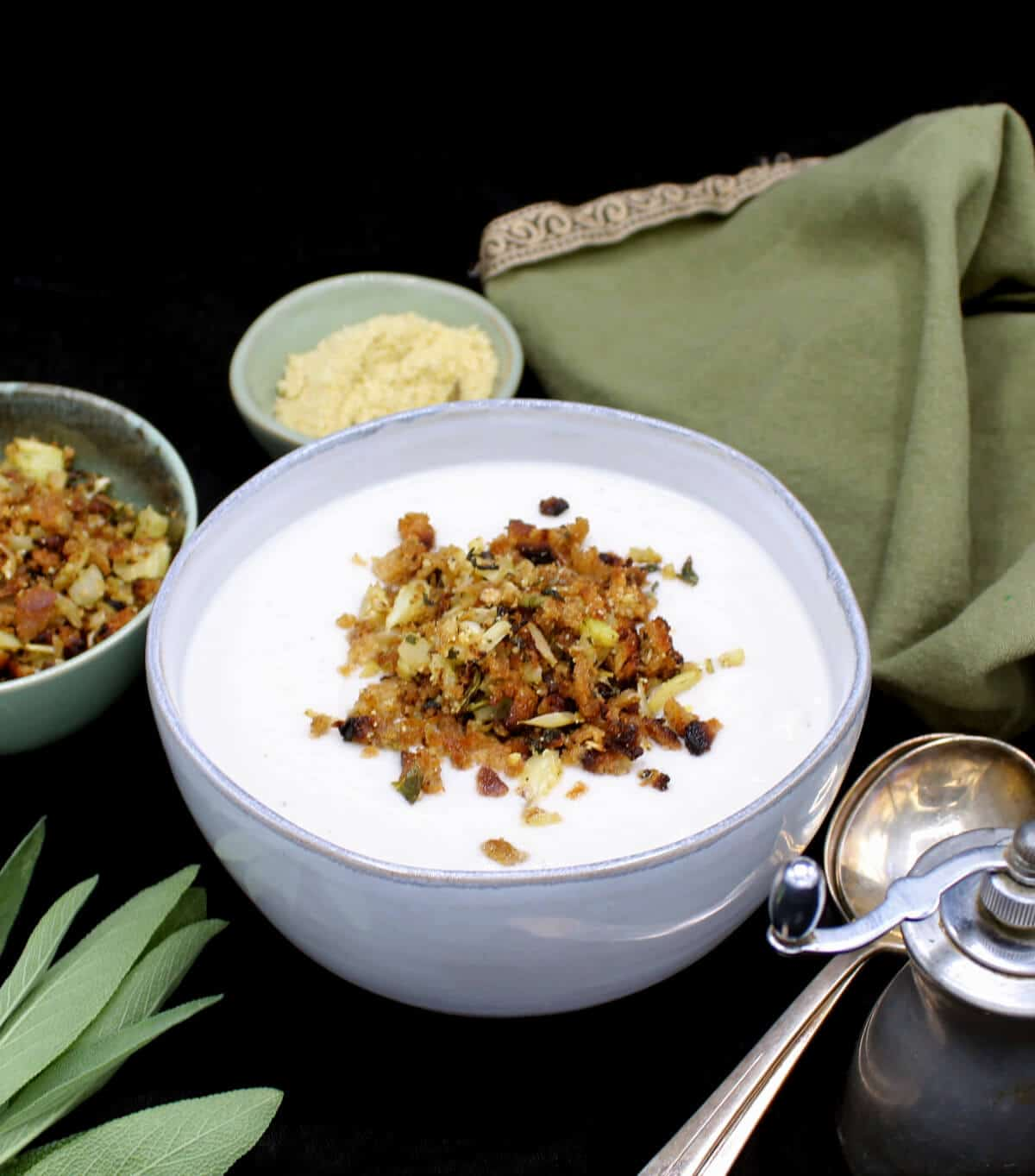 Creamy vegan cauliflower soup in a gray ceramic bowl with crunchy golden breadcrumb topping, with sage leaves, silverware, a pepper grinder and a green napkin next to it.