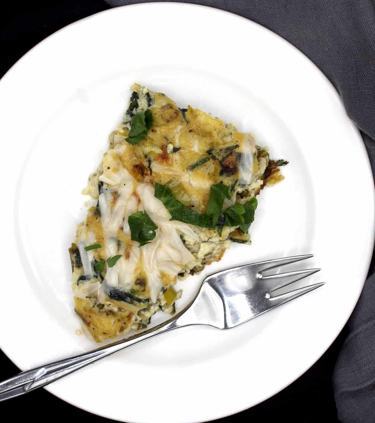 A slice of vegan leek and spinach frittata in a white plate with a steel fork.