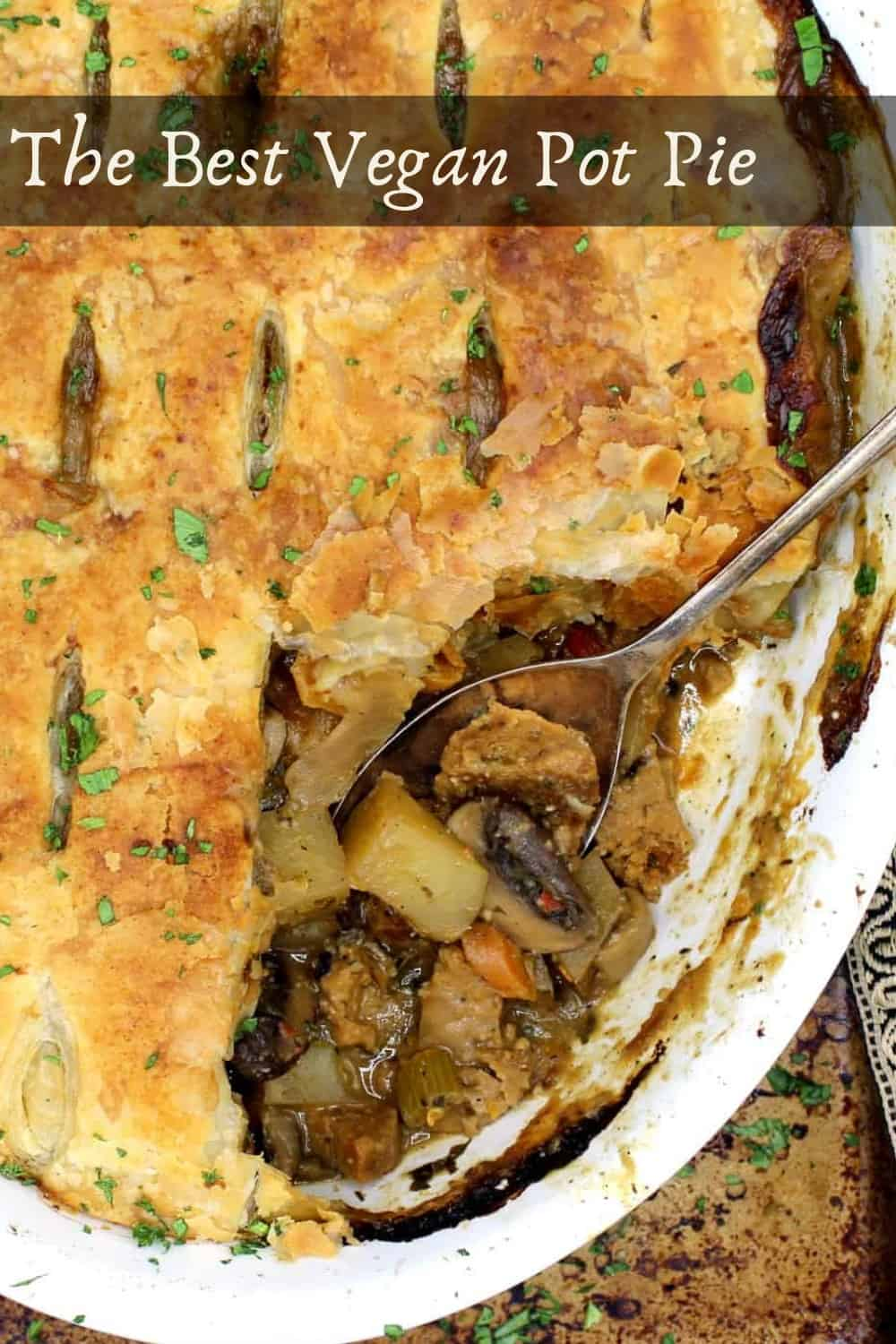 The best vegan pot pie with a crackly, crispy, golden puff pastry crust and a juicy filling of potatoes, mushrooms, squash, sausage and more veggies baked in a white oval baking dish with a steel spoon.