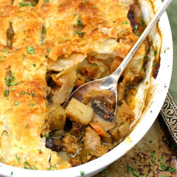 An oval white baking dish with a pot pie that has a golden puff pastry crust and a filling of carrots, potatoes, onions, celery, squash, mushrooms and sausage, all on a baking sheet