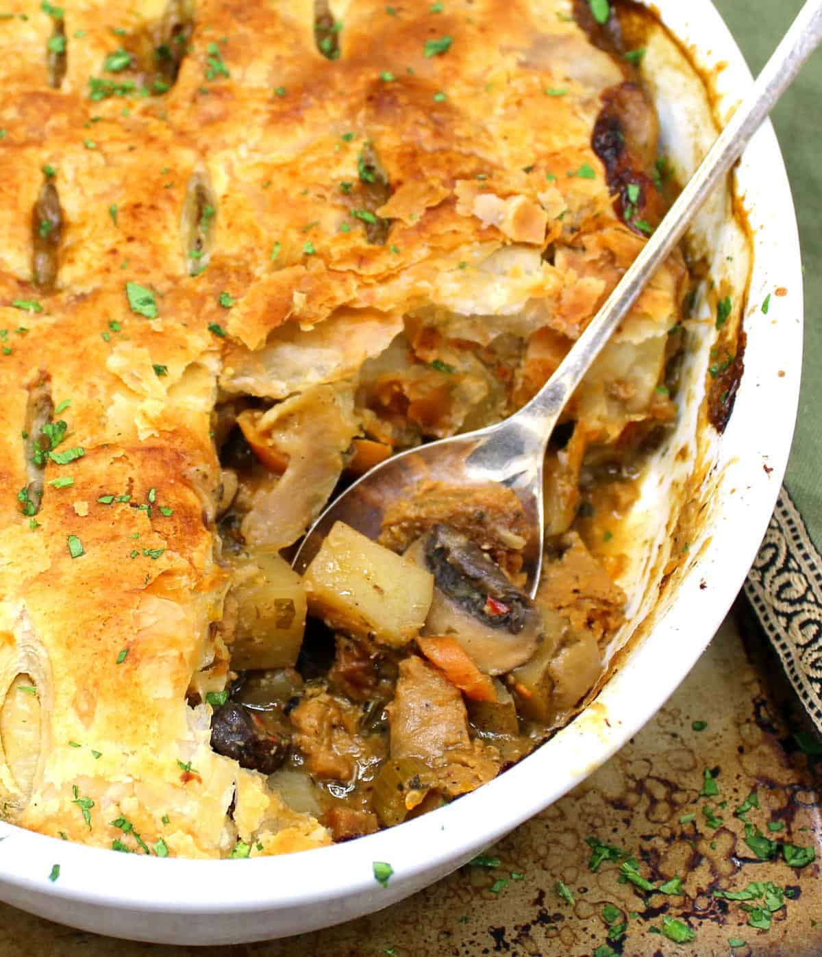 An oval white baking dish with a vegan pot pie that has a flaky golden crust made of puff pastry, with a filling of potatoes, mushrooms, carrots, onions, herbs and sausage on a baking sheet with a green napkin