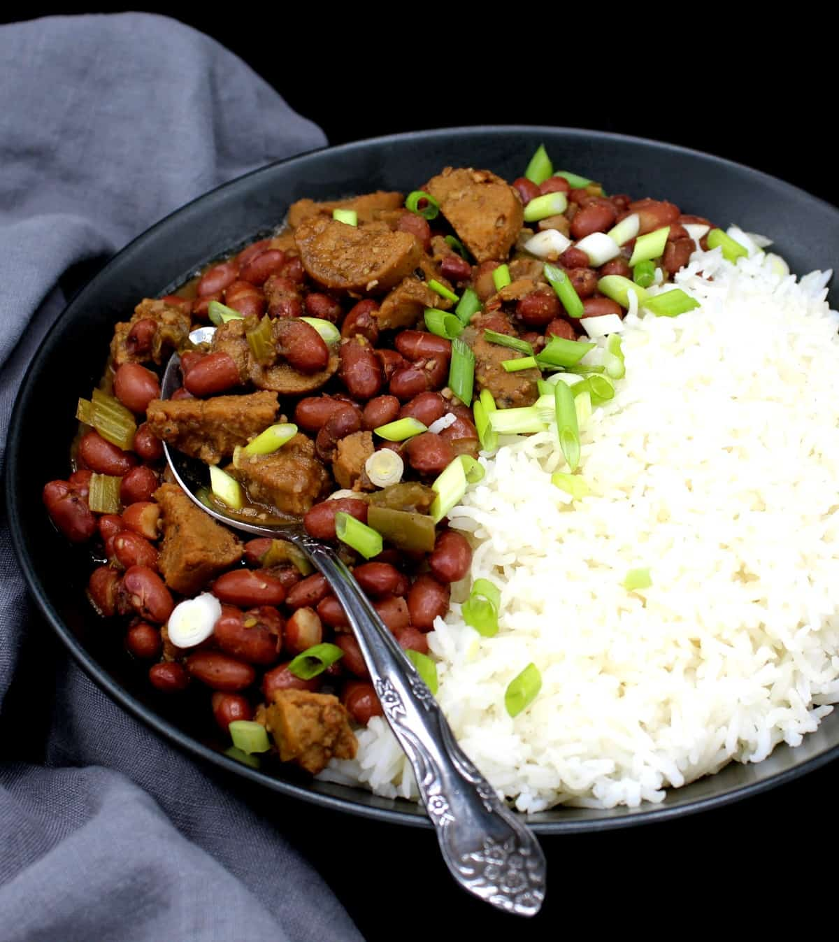 A closeup of vegan red beans and rice garnished with scaliions in a black bowl with a decorative spoon against a gray napkin