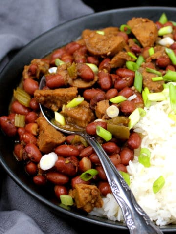 Vegan red beans and rice in a black bowl with a decorative spoon against a gray napkin
