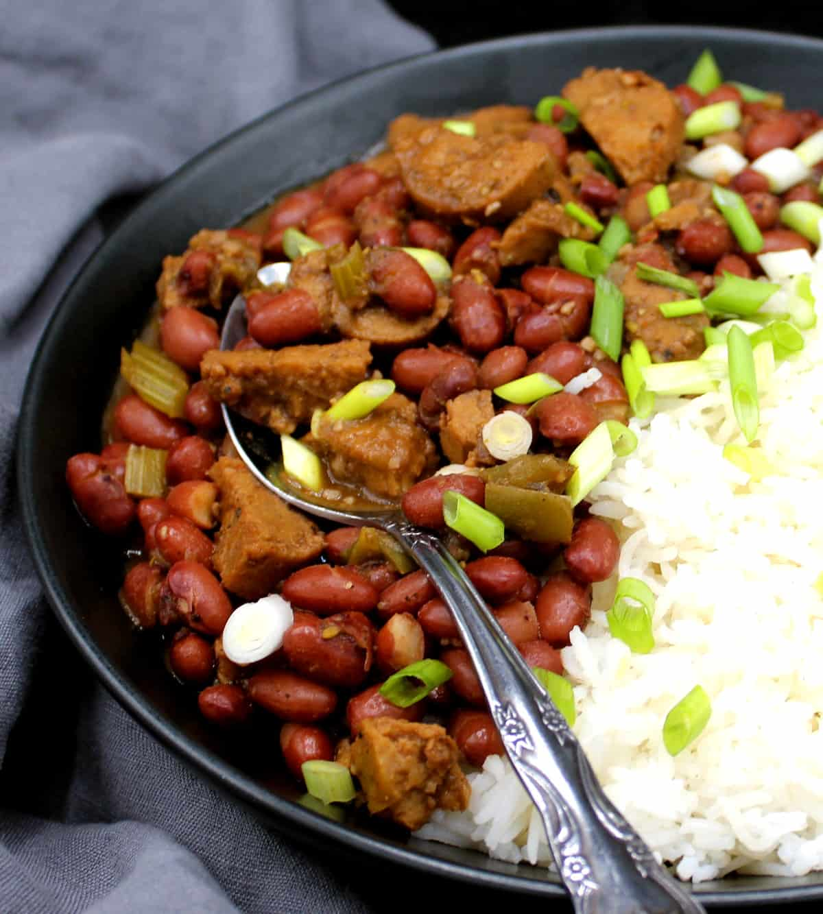 A closeup of vegan red beans and rice garnished with scallions in a black bowl with a decorative spoon against a gray napkin