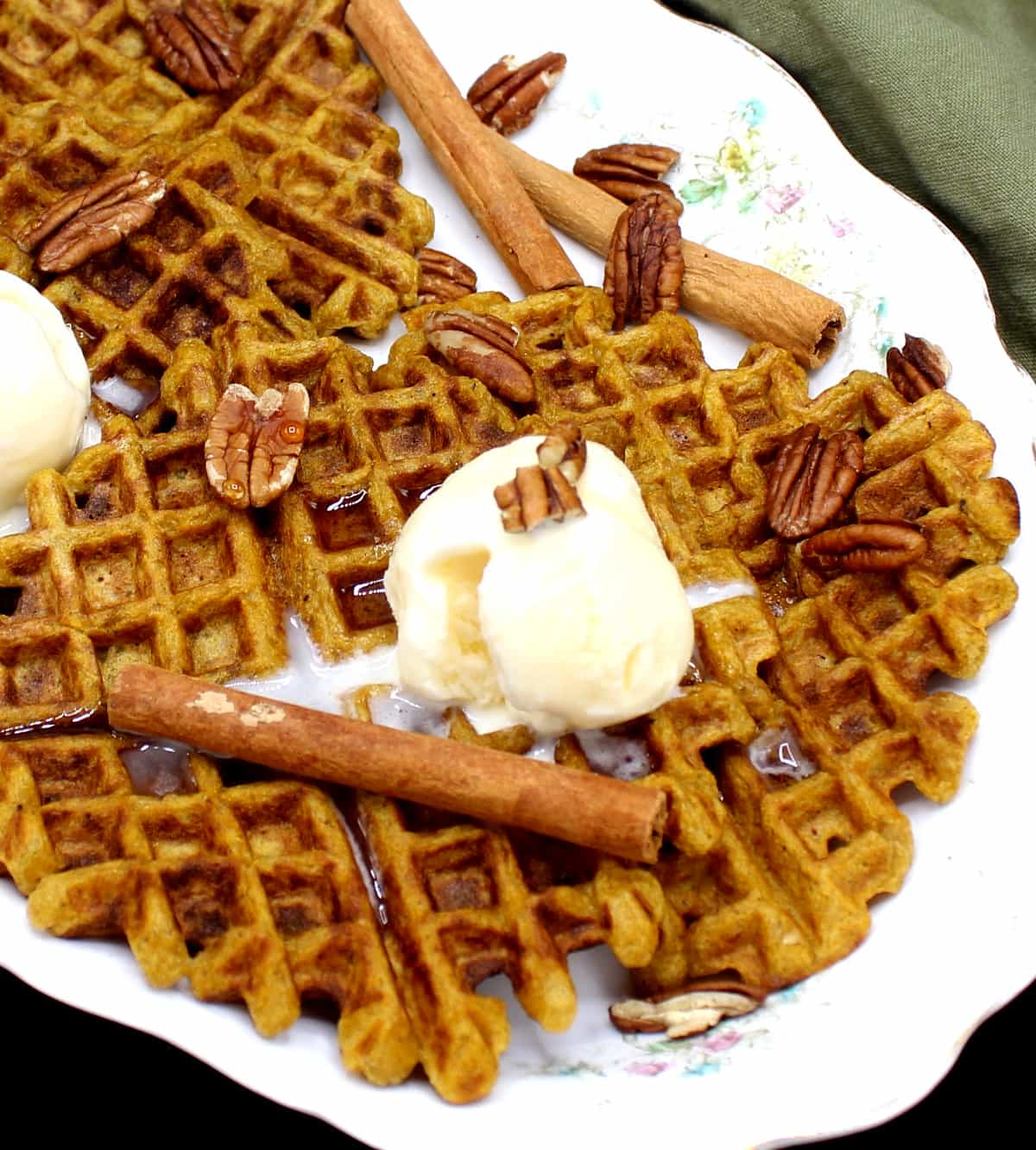 Vegan Sourdough Pumpkin Spice Waffles on a white oval decorative serving dish with a flower pattern. On top of the waffles is vanilla ice cream and sticks of cinnamon and pecans are scattered around.