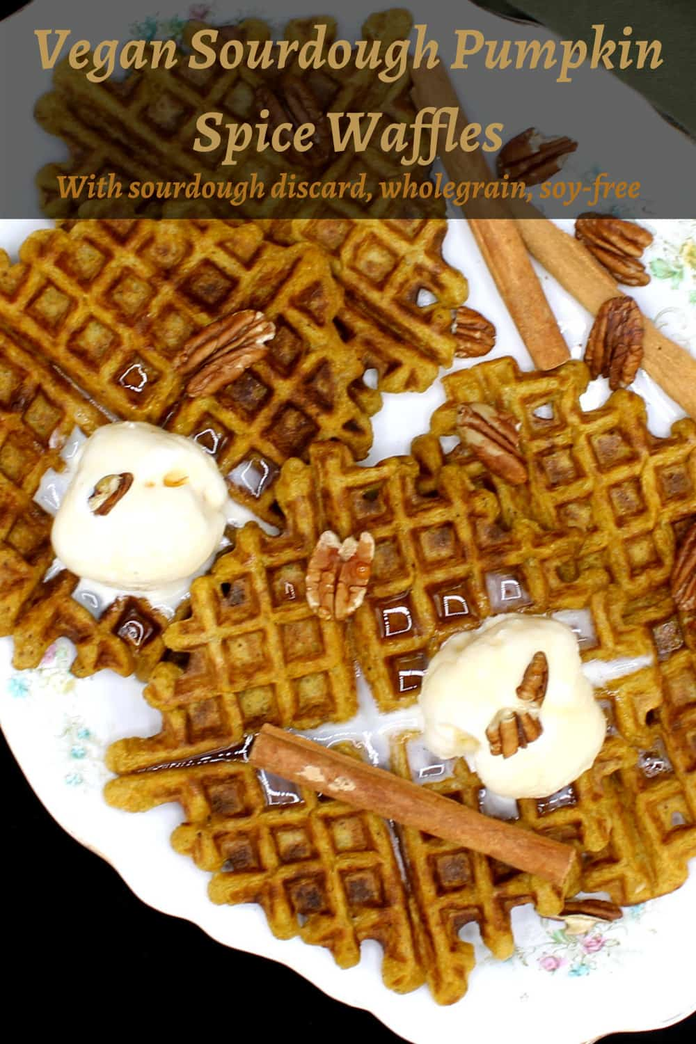 Vegan Sourdough Pumpkin Spice Waffles on a white serving dish with a flower pattern. On top of the waffles is vanilla ice cream and sticks of cinnamon and pecans are scattered around.