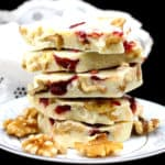 A stack of vegan white chocolate bark or candy pieces with raspberry and walnuts in a white and blue porcelain plate